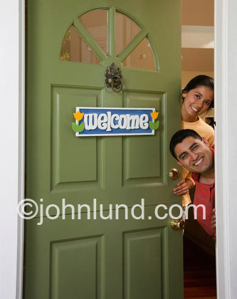 Happy Hispanic Couple Looking Out Their Front Door